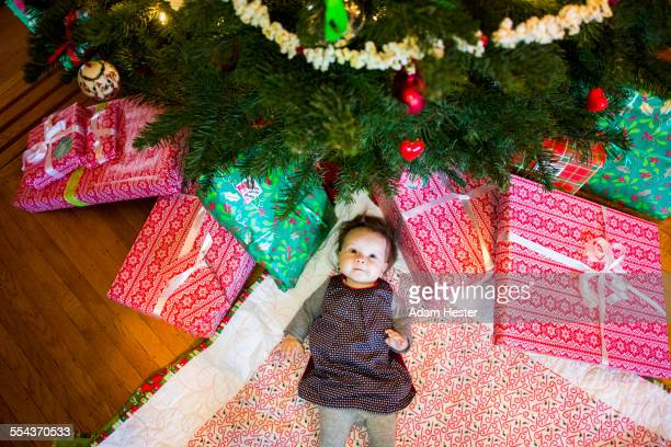 High angle view of Caucasian baby girl laying under Christmas tree
