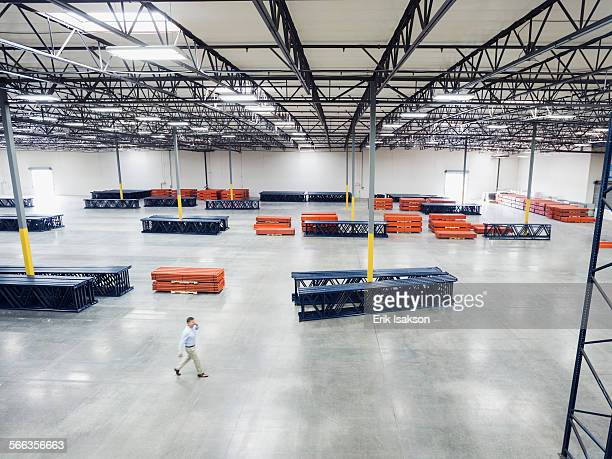High angle view of Caucasian businessman walking in empty warehouse