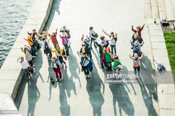 High angle view of Caucasian children waving from waterfront
