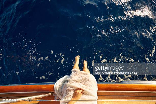High angle view of Caucasian woman dangling feet over boat deck