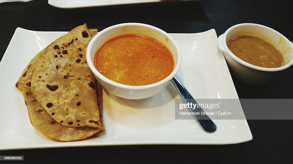 High Angle View Of Chapatti With Curry Served On Table