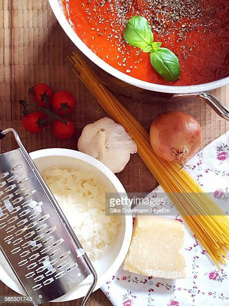 High Angle View Of Cheese With Spaghetti And Sauce On Table