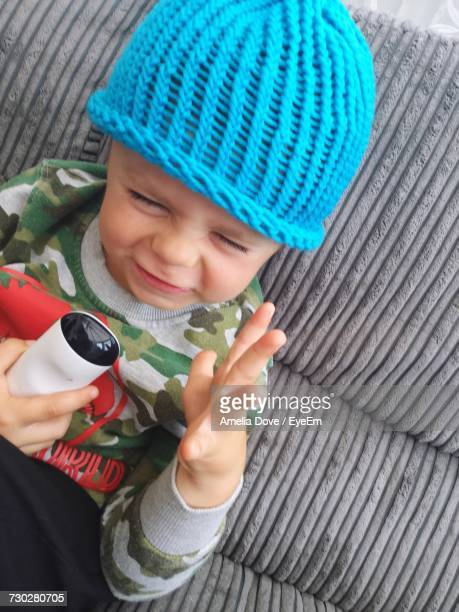 High Angle View Of Child Making Face While Sitting On Sofa