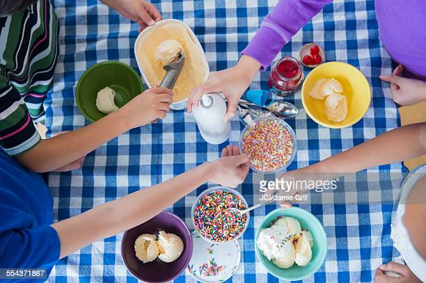 High angle view of children making ice cream sundaes