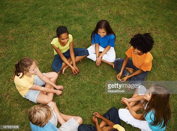 Vue grand angle d'enfants assis sur l'herbe