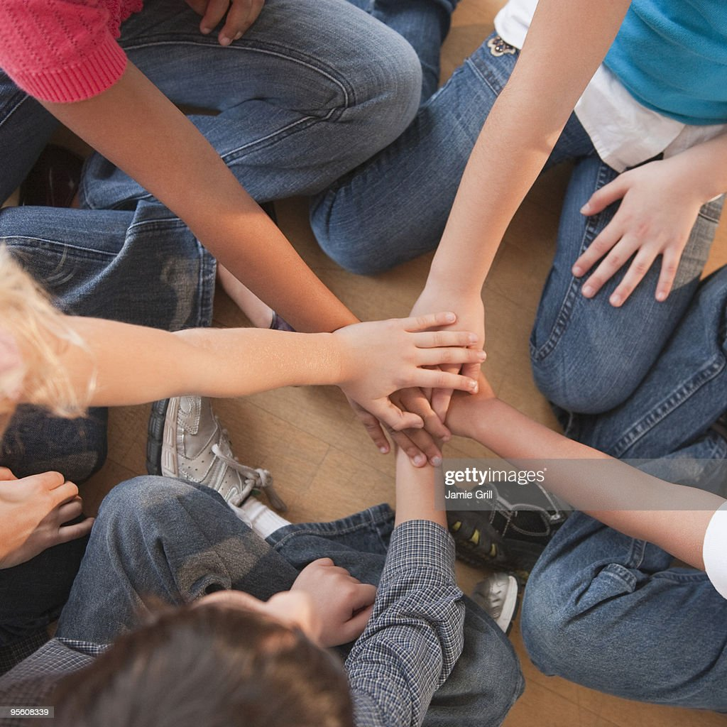 High angle view of children's hands stacked