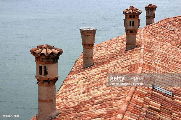 High Angle View Of Chimneys On Roof By Sea