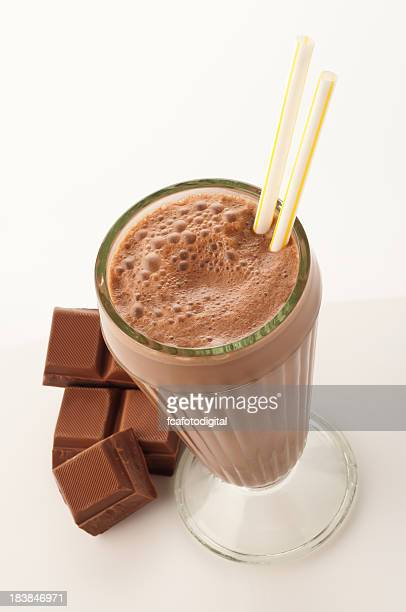 High angle view of chocolate milkshake glass on white backdrop