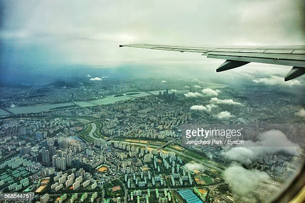 High Angle View Of City And Airplane Wing Seen Through Airplane Window