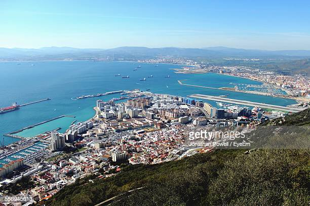 High Angle View Of Cityscape By Sea Against Clear Blue Sky