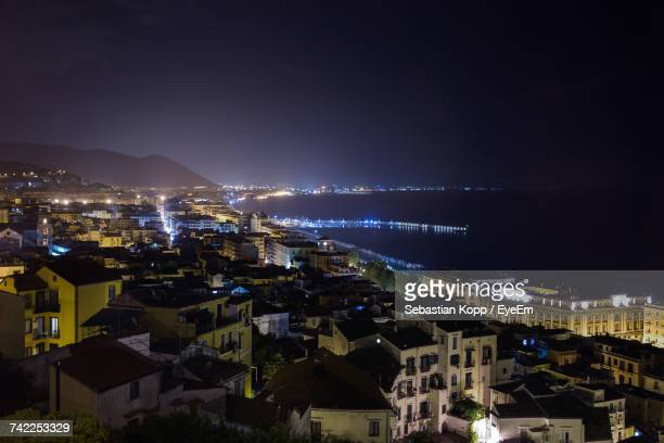 High Angle View Of Cityscape By Sea During Night