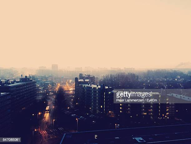 High Angle View Of Cityscape In Foggy Weather At Dawn Against Clear Sky