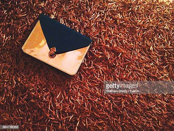 High Angle View Of Clutch Bag On Dry Grass