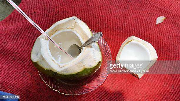 High Angle View Of Coconut Water With Drinking Straw And Spoon On Red Sheet