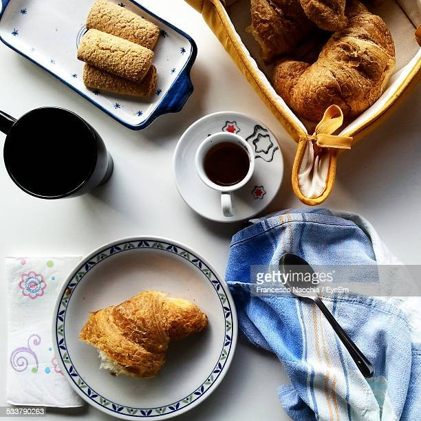 High Angle View Of Coffee And Croissant With Cookie On Table