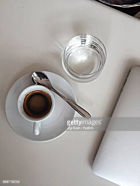 High Angle View Of Coffee Cup By Drinking Glass On Table