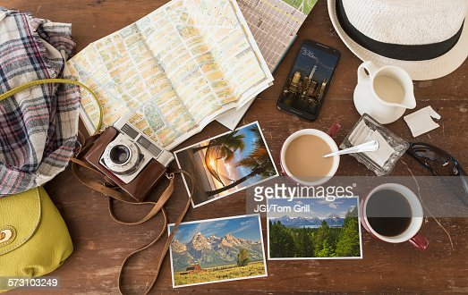 High angle view of coffee, maps, photographs, camera and cell phone : Stock-Foto