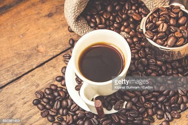 High Angle View Of Coffee Served In Cup By Beans On Wooden Table