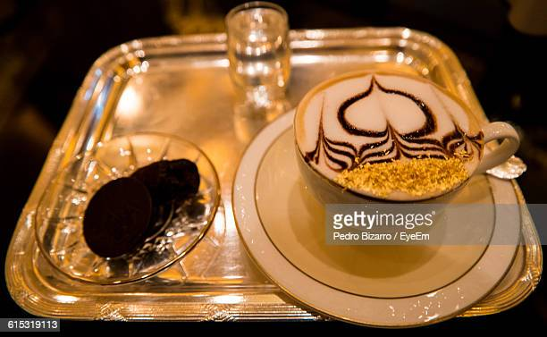 High Angle View Of Coffee With Froth Art On Serving Tray