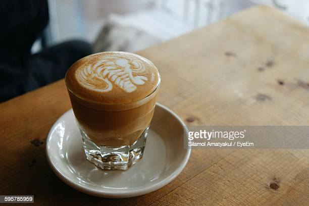 High Angle View Of Coffee With Froth Art Served On Table