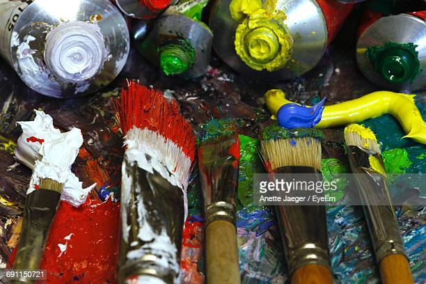 High Angle View Of Colorful Paintbrushes And Paint Tubes