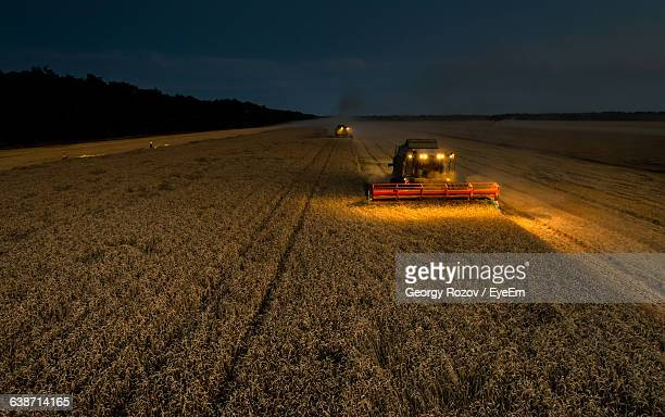 High Angle View Of Combine Harvester On Field At Night