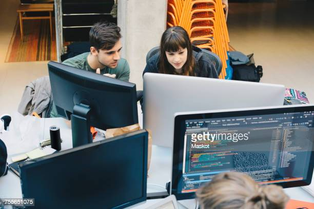 High angle view of computer programmers using desktop PC at office desk