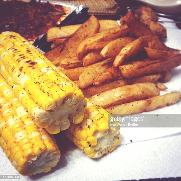 High Angle View Of Corns And Fried Potatoes
