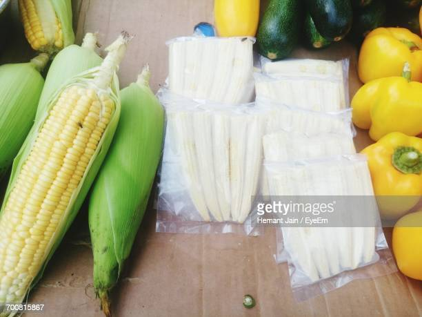 High Angle View Of Corns By Yellow Bell Peppers For Sale At Market Stall