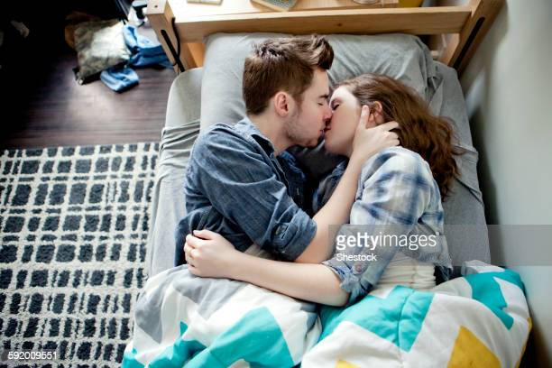 High angle view of couple kissing on bed