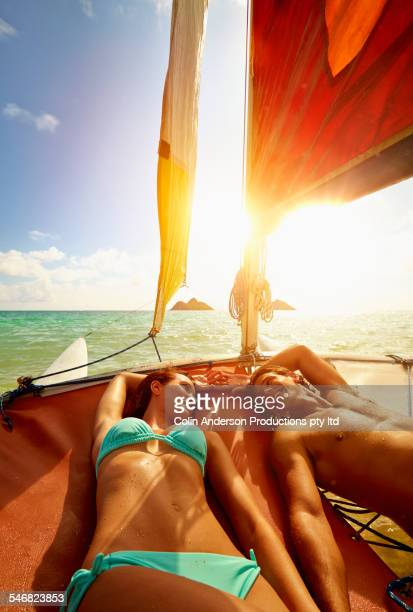 High angle view of couple laying on sailboat