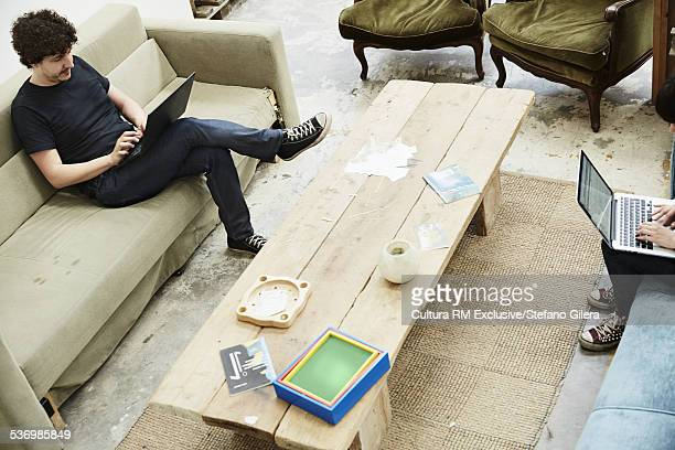 High angle view of couple on opposite sofas typing on laptops
