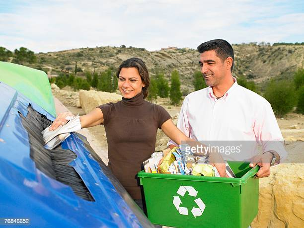 High angle view of couple placing papers in a recycle bin, husband holding box full of papers, Alicante, Spain,