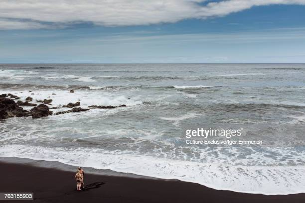 High angle view of couple standing on black beach at Puerto de la Cruz, Tenerife, Canary Islands