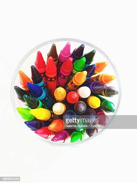 High Angle View Of Crayons In Container Against White Background