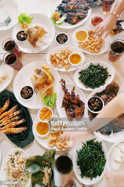 High Angle View Of Cropped Hands Over Various Food Served In Plates On Table
