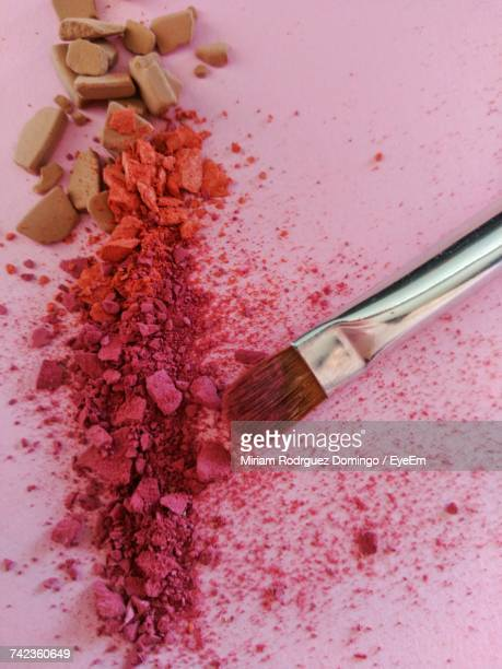 High Angle View Of Crushed Powder Compact With Make-Up Brush On Table