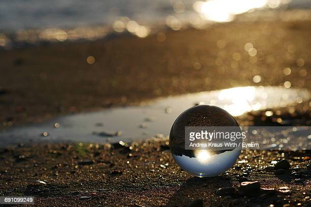 High Angle View Of Crystal Ball With Reflection At Beach During Sunset