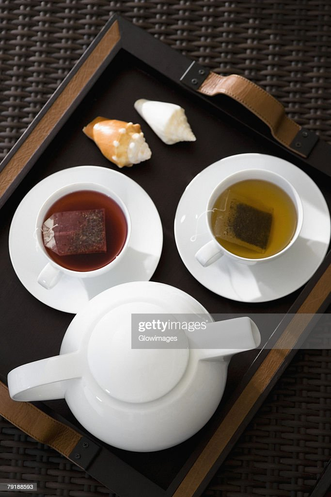 High angle view of cups of herbal tea with a teapot on a serving tray : Foto de stock