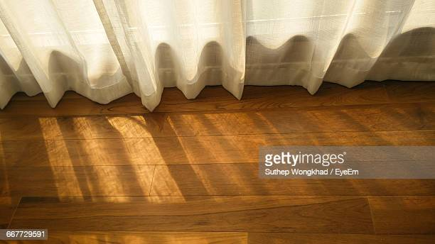 High Angle View Of Curtains Hanging Over Hardwood Floor