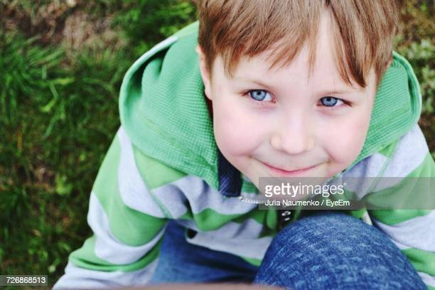 High Angle View Of Cute Boy Sitting On Grass