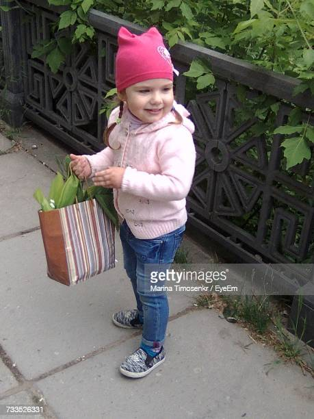 High Angle View Of Cute Girl Holding Bag With Leaves While Standing On Footpath