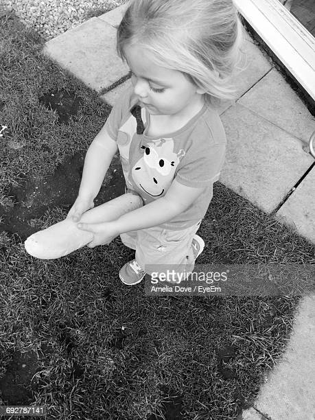 High Angle View Of Cute Girl Holding Bread While Walking In Yard
