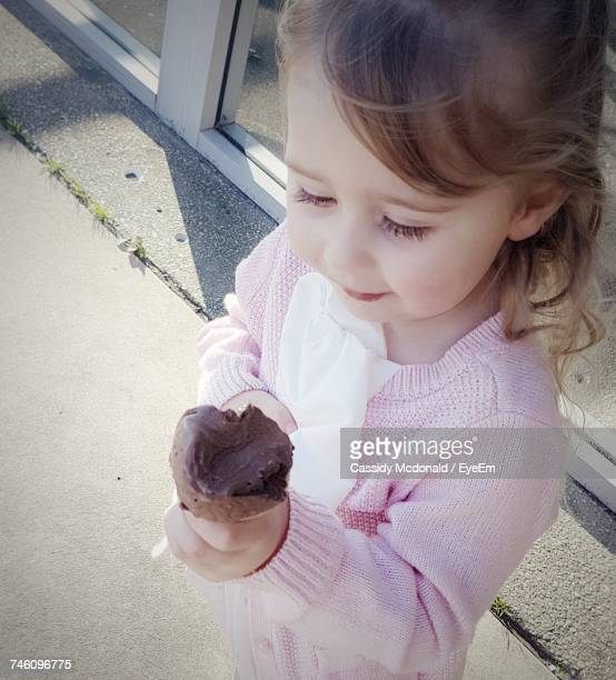 High Angle View Of Cute Girl Holding Ice Cream Outdoors