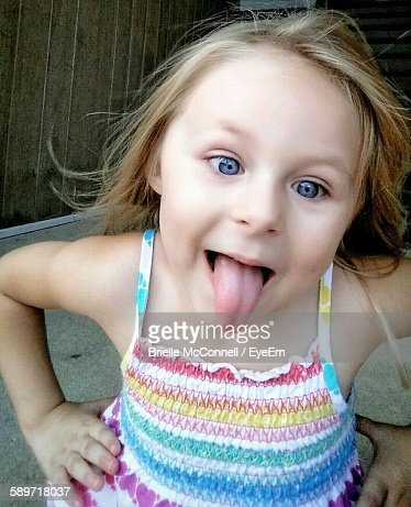 High Angle View Of Cute Girl Sticking Out Tongue
