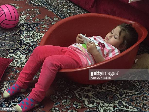 High Angle View Of Cute Girl Using Phone In Container On Rug At Home