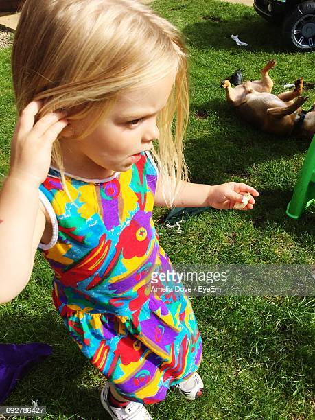 High Angle View Of Cute Girl With Hand In Hair At Park