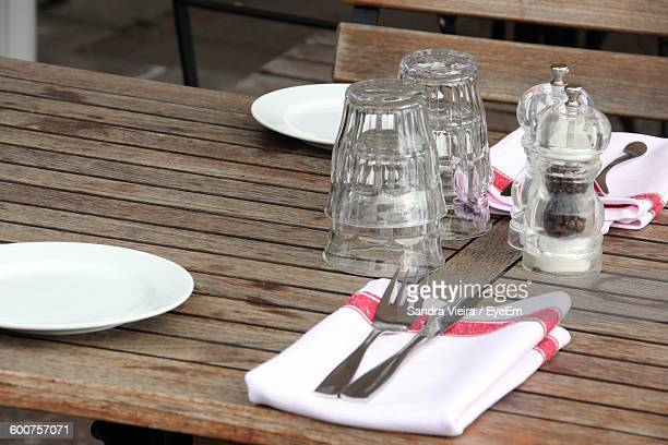 High Angle View Of Cutlery With Ingredients Bottles On Table In Restaurant