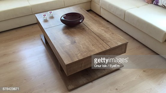 High Angle View Of Decorative Bowl On Wooden Coffee Table Amidst Sofa In Living Room