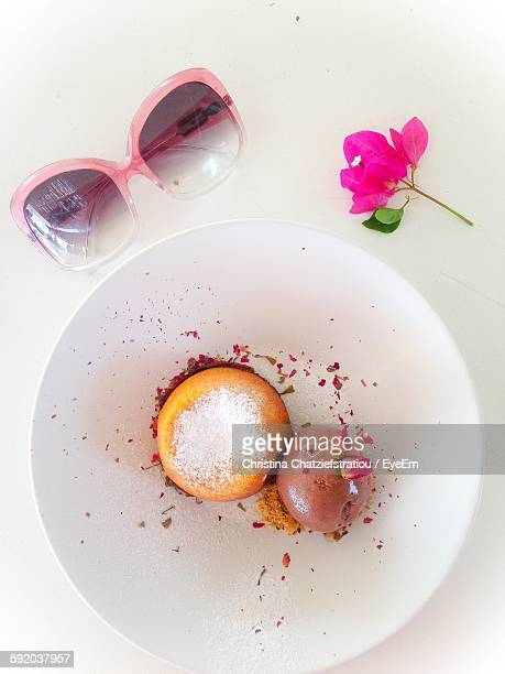 High Angle View Of Dessert Souffle With Pink Flower And Sunglasses On Table